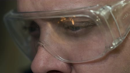 fabrico : A 30s Man Does Welding in Glasses Close-up with a Reflection of Sparks in 4K.