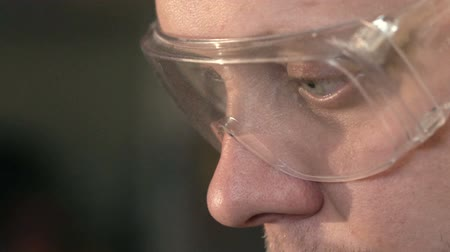 kaynakçı : Guy Close-up at the Factory Looks at his Detail in Glasses Slow Motion