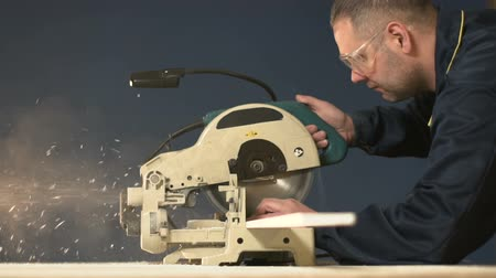 golenie : A Man on a Blue Background Lowers the Saw and Processes the Slow Motion Tree Wideo