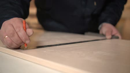 instrument maker : Furniture Maker at the Plant Marks an Iron Ruler Close up with Pencil Slowmotion