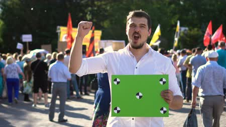 picketing : Man Against the Background of a Crowd Rallies with a Transporter for Tracking 4K Stock Footage