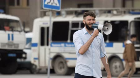 public worker : Speaker speaks into loudspeaker on street in city. Person communicates with people through a megaphone outside. A smiling guy is fun talking to crowd of outdoor. Police car or bus in background 4k.