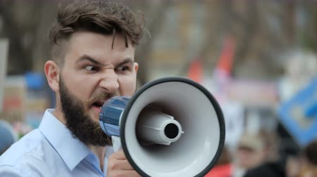 мегафон : A desperate man goes and demands a megaphone on strike. European guy with a beard is yelling into the loudspeaker at a rally. People are unhappy with the government. Revolution on the street in city.