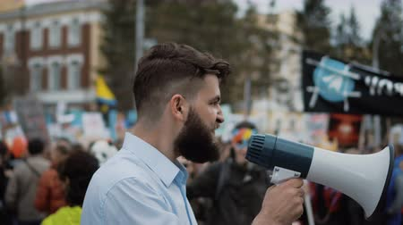 transação : Young adult angry man goes and shouts in a megaphone on strike. Caucasian guy with a beard yelling into the loudspeaker at the rally. Office worker displeased with dismissal or reduction.