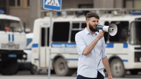 paddy wagon : The protest of people on the street against the background of a patrol car. Angry guy screaming into a megaphone in city and looking at the camera. Angry guys on the background of Police Paddy Wagon.
