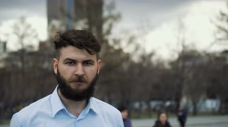 güvenilirlik : A serious man with a beard and mustache looks into the camera close-up. The look of the guy in the blue shirt is a closeup. Portrait of an office worker in the park. Young adult boy outside in city.