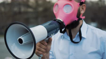 respirator : Caucasian man in a pink gas mask shouts into a megaphone close-up. People at a rally in the city speaks into a loudspeaker closeup. The guy takes off his mask and looks into the camera 4k. Stock Footage