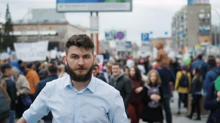 мегафон : Young adult angry man goes and shouts in a megaphone on strike. Caucasian guy with a beard yelling into the loudspeaker at the rally. Office worker displeased with dismissal or reduction slow mo..