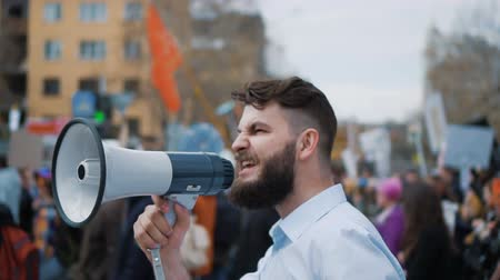 verdadeiro : Young adult angry man goes and shouts in a megaphone on strike. Caucasian guy with a beard yelling into the loudspeaker at the rally. Office worker displeased with dismissal or reduction slow motion.