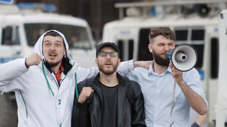 мегафон : The protest of people on the street against the background of a police car. Angry guy screaming into a megaphone in the city and look at the camera. Angry guys on the background of a police vehicle