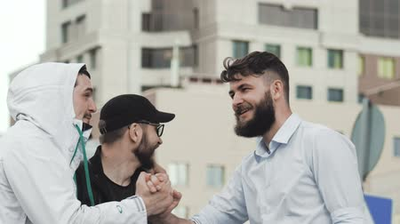 slapping : Gay man gave five to a friend close-up. Meeting friends on the street in the city closeup. People are talking. The man shakes hands with his friends and smiles. Drunk funny people laugh close up. Stock Footage