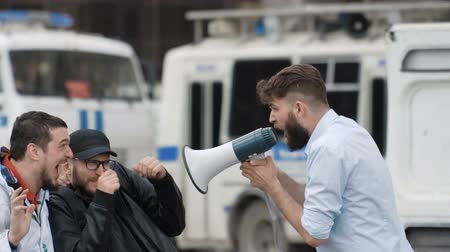 subordinate : An angry man with a beard shouts loudly at people in a megaphone. young adult boy yelling into a bullhorn at the guys outside in the city. The boss shouts at his subordinate workers during the day.