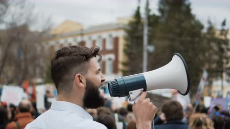 blm : Young adult angry man goes and shouts in a megaphone on strike. Caucasian guy with a beard yelling into the loudspeaker at the rally. Office worker displeased with dismissal or reduction.