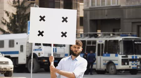 picketing : One bearded european guy on the background of a police car holds a banner in hand and look at camera. Protest 1 caucasian man on street in city. Serious one human picketing on background of bus cops. Stock Footage