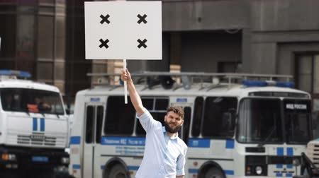 transação : One bearded european guy on the background of a police car holds a banner in hand and look at camera. Protest 1 caucasian man on street in city. Angry one human picketing on background of bus cops 4k. Stock Footage
