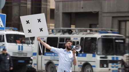 oposição : One bearded european guy on the background of a police car holds a banner in hand and look at camera. Protest 1 caucasian man on street in city. Angry one human picketing on background of bus cops 4k. Vídeos