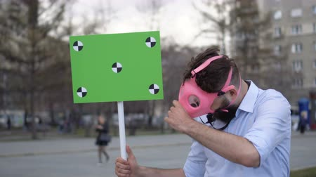 A young adult at a demonstration or strike looking into camera. A serious guy takes off a pink gas mask on the street in city. A cool crazy protester at rally. A crazy man with a poster close-up 4k.