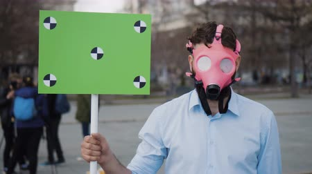 tracking : A young adult at a demonstration or strike looking into camera. A serious guy takes off a pink gas mask on the street in city. A cool crazy protester at rally. A crazy man with a poster closeup 4k. Stock Footage