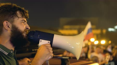 unrest : Guy in green T-shirt and loudspeaker is making speech at rally. An angry man gives strong speech to crowd on Maidan. beginning of revolution. man near car and with mouthpiece agitates at rally. Stock Footage