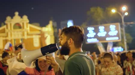 won : guy in green T-shirt rejoices at street party in night city winning football. Russia won. Atmospheric celebration in honor of victory. guy goes into crowd jump and rejoice with crowd victory of Russia Stock Footage