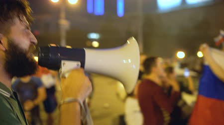 unrest : An angry man at a rally agitates with the crowd. A guy in a green T-shirt and a loudspeaker is making speech at rally. An angry man gives strong speech to crowd on Maidan. beginning of revolution. Stock Footage