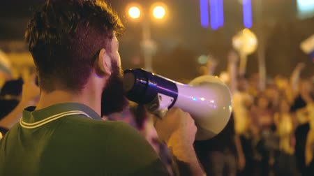unrest : A guy in a green T-shirt and a loudspeaker is making a speech at the rally. An angry man gives strong speech to crowd on Maidan. beginning of revolution. An angry man at a rally agitates with crowd. Stock Footage