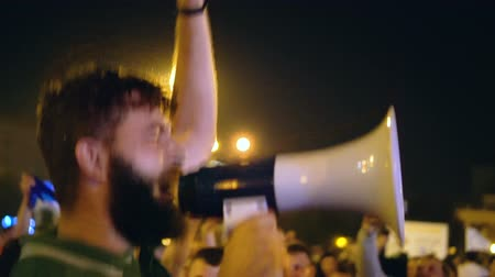megafon : A young guy comes out from the loudspeaker for the crowd against the current government. A man jumps and lights the crowd at the right atmosphere. In the night city the activist conducts a strike.