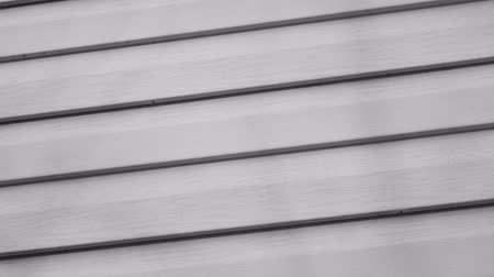 whirling : White siding background of gray panels rotates. Facade of the building 4k close-up. Clear place for your isolated text. Empty space for your title copy space. Copyspace logo to blank design.