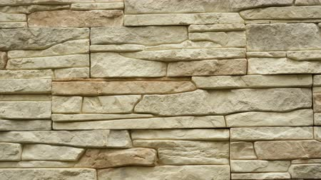 бежевый : Panorama of decorative stone. Move up the granite to the house. Wall of stone. Clear place for your isolated text pattern. Empty space for your title copy space. Copyspace logo to blank design. Стоковые видеозаписи