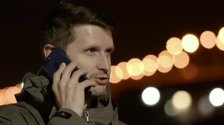 Man talking on the phone against backdrop of the night city. Close up and bokeh effect intensify emotions. The young man is alarmed, he is nervous. His hands are shaking, and his eyes running around.