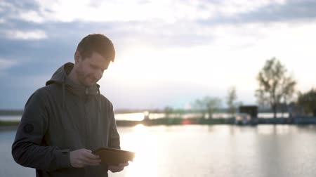 Guy is mailing using tablet or touchscreen. Tourist on the lake and sun lights. Nature is magnificient and sun lishts though clouds. Man is happy and pleasant while he is typing his girlfriend. Стоковые видеозаписи