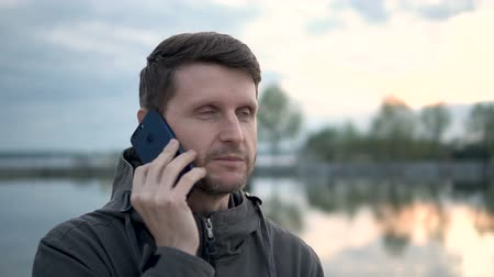 Young adult man talking on phone in the forest near lake. He has a vacation on nature. He is speaking with his mom and he is happy. Close up shows all of his emotions. Lake is calm and sky is blue. Wideo