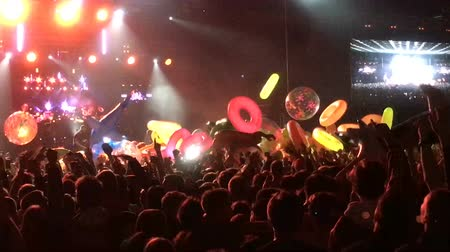 koppintás : Inflatable mattresses and toys are floating at the concert crowd-surfing. Drive and energy on the background of the scene at a rap or rock party. Lifebuoy. Bright beautiful light on the stage 4k. Stock mozgókép