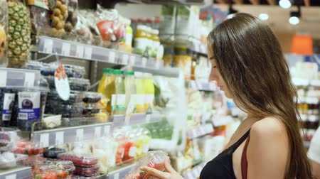 dietético : Beautiful girl model in food store chooses fresh berries for a 4K diet. Cute woman chooses a vegetarian food in a health pack. Brunette with long hair buys fresh fruit at mall. Proper nutrition. Stock Footage