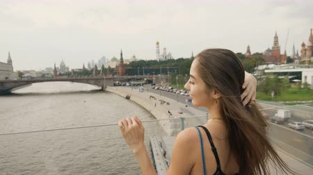 lehkost : Beautiful girl model stand closeup bridge river against background city during day. cute woman look big city from 4K bridge. brunette long hair accelerates with wind background city from public bridge
