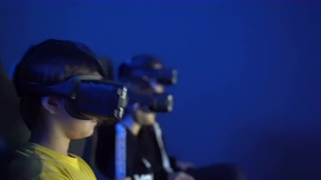 погружение : Children with glasse virtual reality are watching movie in 4K cinema. future digital technology for watching movies. Amusement for kid attention. girl and boy quickly chat in vr chair while they play