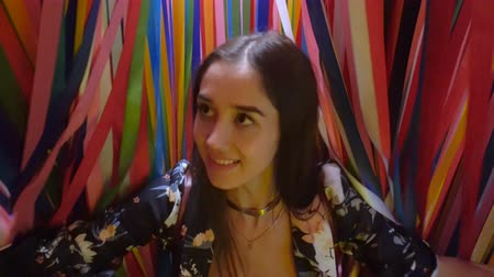 brasileiro : Girl beautiful reveals colorful ribbon and peeps 4K. Pretty woman first time to know world, looking at the camera. Brazilian tape give effect of ecstasy. Happy girl with pleasure exploring environment