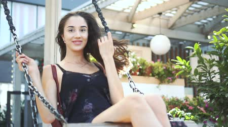 lehkost : Young girl model look swinging on swing in slowmotion. Fashionable girl spend bright sunny day in summer on swing closeup. Beautiful woman happy to be on swing like child smiling and looking at camera Dostupné videozáznamy