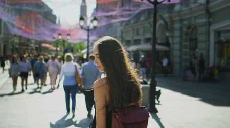 ура : The girl walks along the street of a populous city in slow motion. woman turns and looks at camera while walking in afternoon along city street. girl smiles at camera and offers to follow me