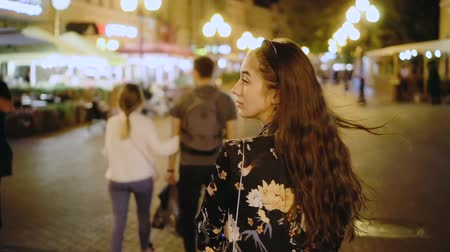 ура : Beautiful girl model walks through the night city in slow motion. happy woman is walking along street of night megalopolis. girl turn and look at camera in middle of night cityscape. Nightlife youth