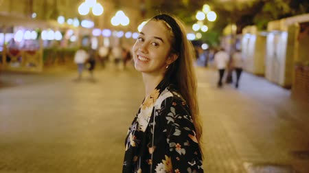 ура : Happy woman is walking along street of night megalopolis. Beautiful girl model walks through the night city in slow motion. girl turn and look at camera in middle of night cityscape. Nightlife youth Стоковые видеозаписи