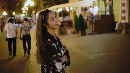ура : Girl turn and look at camera in middle of night cityscape. Beautiful girl model walks through the night city in slow motion. happy woman is walking along street of night megalopolis. Nightlife youth