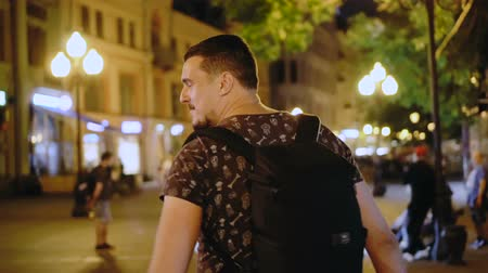 ура : A guy walks through the night city closeup in slow motion. The happy man rejoices at the night atmosphere of the metropolis. The dude turns around and looks at the camera happily. Nightlife youth. Стоковые видеозаписи
