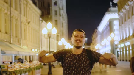 hafifletmek : Dude is looking at camera and happy for victory of football team. The guy walks along the street of the night city and rejoices at the victory. man raises his hands for joy and smiles. Nightlife youth