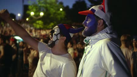 euforia : Football fan shouts, rejoices goal favorite team. Person paint face jump in delight victory match. Closeup guy screaming furiously, jumping with friend against backdrop crowd winning football game.