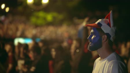 bewilderment : Closeup Russian fan lost bet on sport, very angry with game team. Guy with paint on face lost lot money, took head from terrible match. People angrily look losing their team bet on it. Loss money 4k.