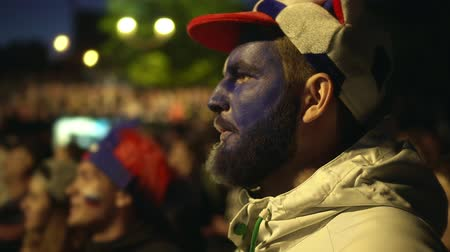 asthma : Man of European football team coughs off flu at football stadium night. fan of team fell ill with infection on background crowd of fans. guy with paint on his face watching sport game, coughs for cold