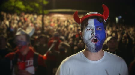 euforia : Football fan shouts, rejoices goal favorite 4K team. Person paint face jump in delight victory match. Closeup guy screaming furiously, jumping with friend against backdrop crowd winning soccer game 4k