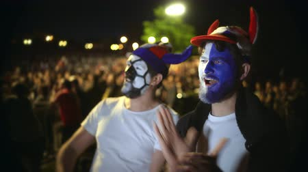 euforia : Football fan shouts, rejoices goal favorite 4K team. Person paint face jump in delight victory match. Closeup guy screaming furiously, jumping with friend against backdrop crowd winning football game