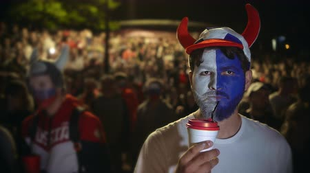 взял : Fan English football team watch match interest, actively drink hot coffee night. man front crowd fan in stadium took black coffee from spectacle. Mug hot coffee in guy hand paint face in sport game Стоковые видеозаписи